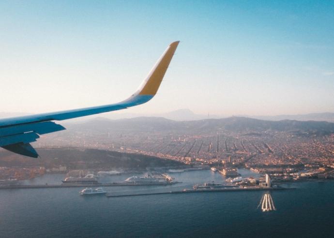Vista de Barcelona en el atardecer, desde un avión, ala del avión parcialmente visible